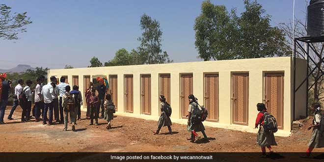 Students walk past the new constructed toilet bloc at a Nashik school