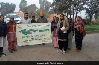 The team holding a banner on open defecation