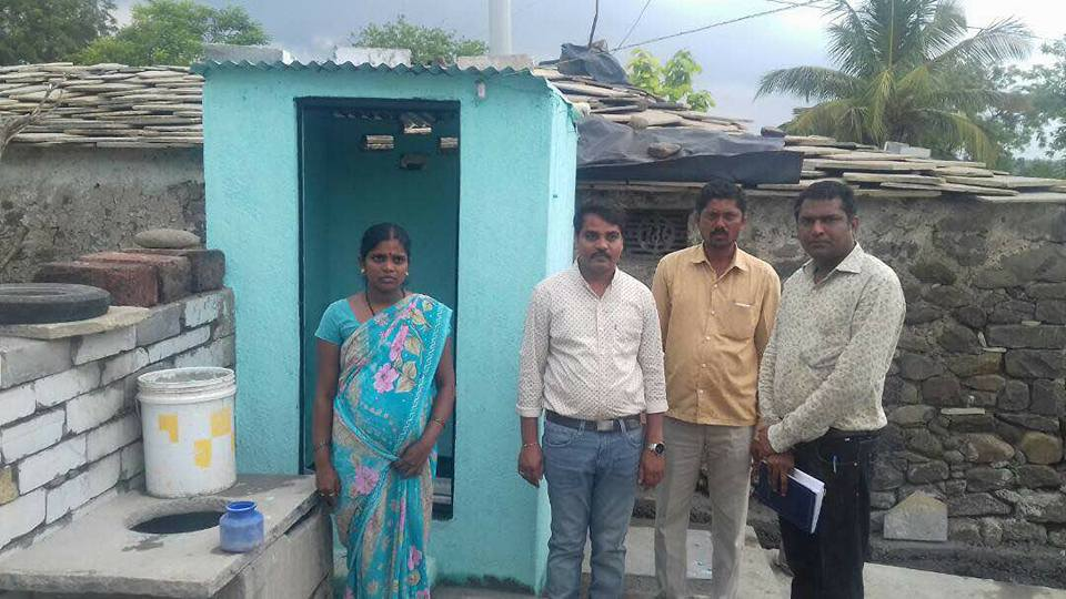 District officials with a constructed toilet