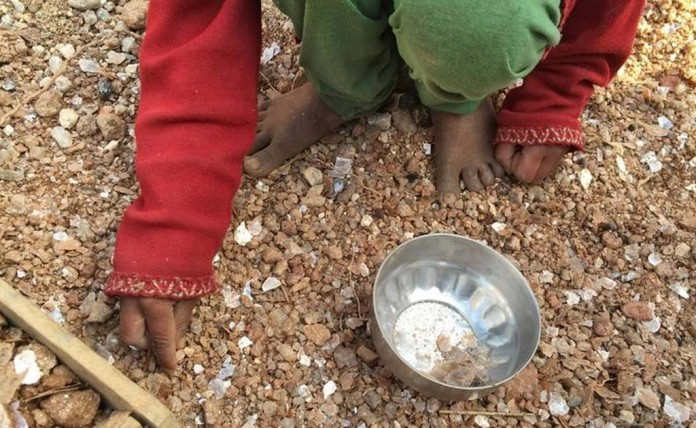 Girl collects mica flakes