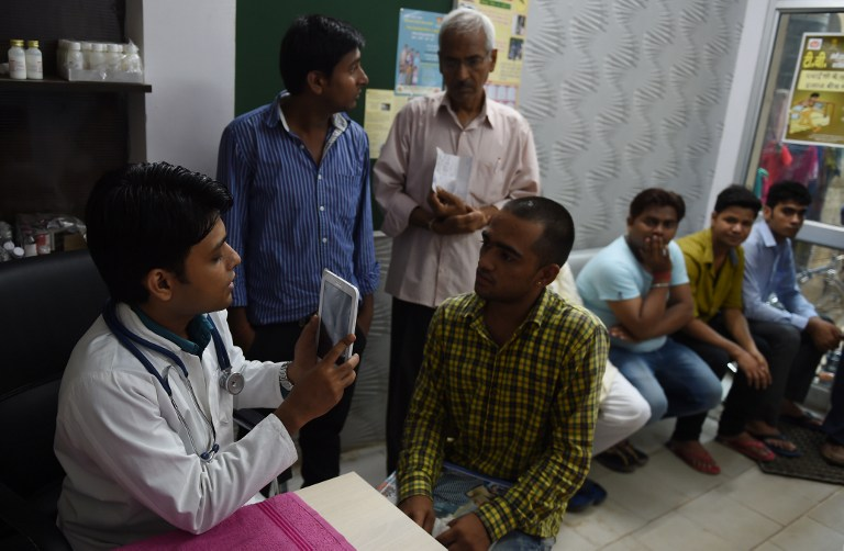 Doctor uses a tablet device to take a picture of a patient for his record in New Delhi.