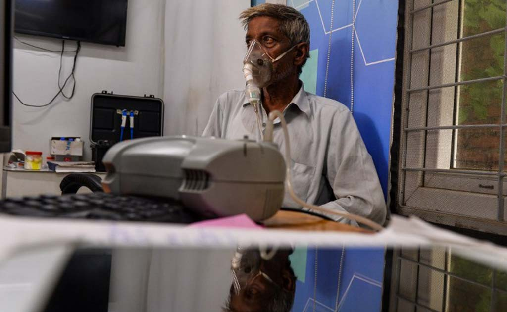 Mohan Lal breathes through a nebuliser at the mohalla clinic in his neighbourhood in New Delhi.