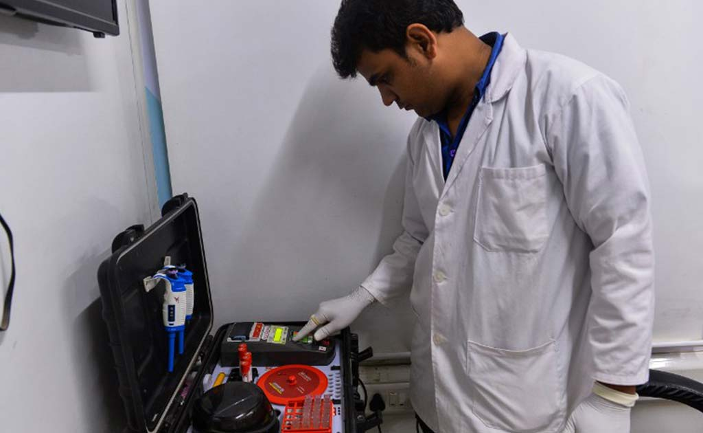A doctor checks vialls of blood at the clinic in Mr Lal's neighbourhood in New Delhi.