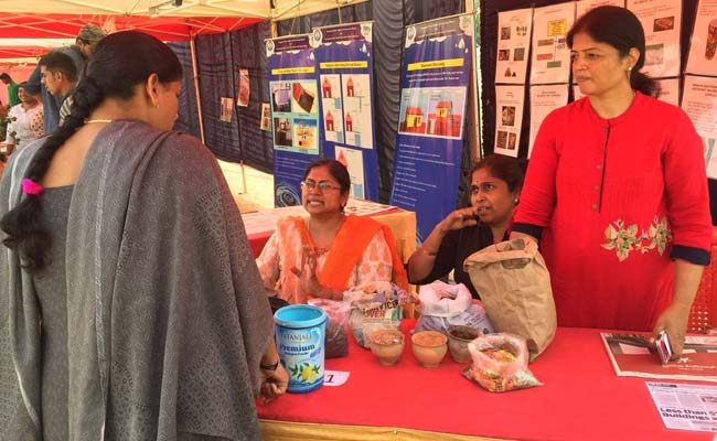 Members of Marali Mannighe talking about waste composting at a DIY compost stall at an event in Bengaluru